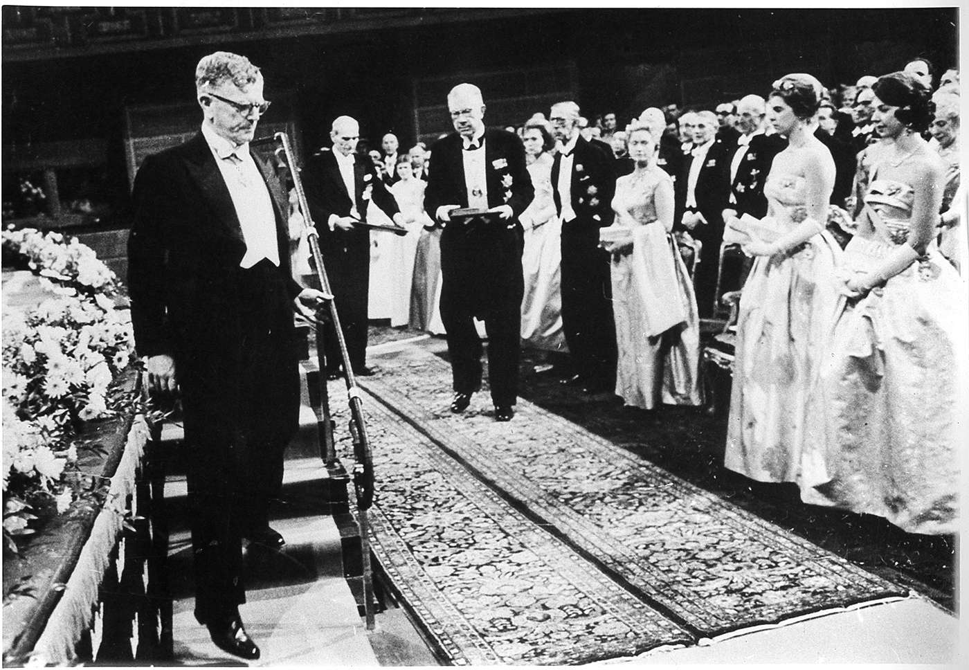 Black and white photograph of Burnet stepping down from a podium at the Nobel Prize award presentation ceremony.