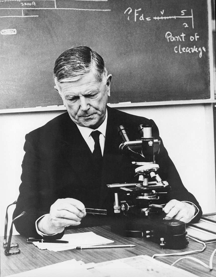 Black and white image of Burnet sitting at a microscope, looking at a slide, a blackboard with equations hangs on the wall behind.