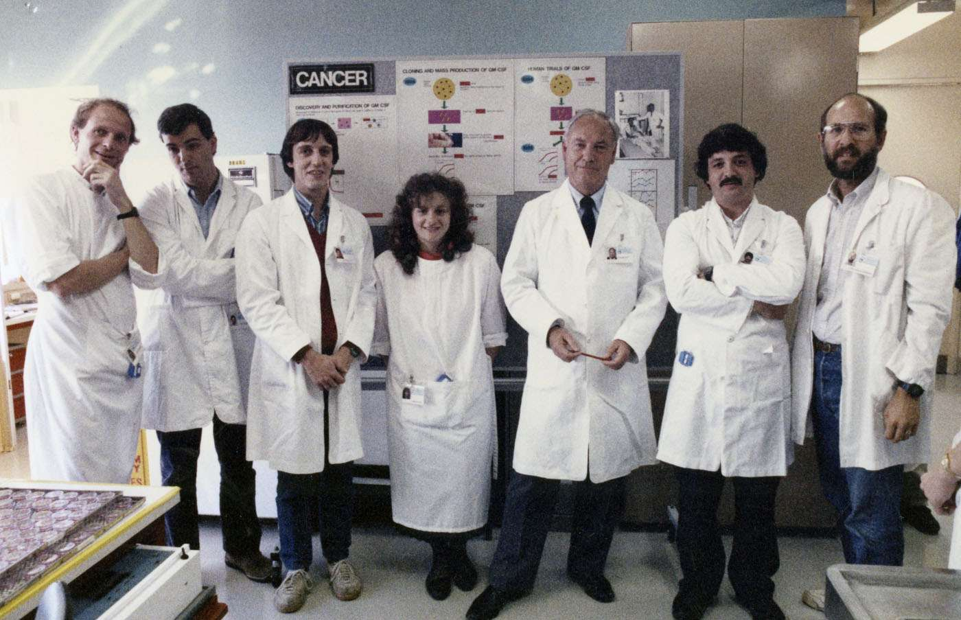 Scientists stand in an office, all wearing lab coats.