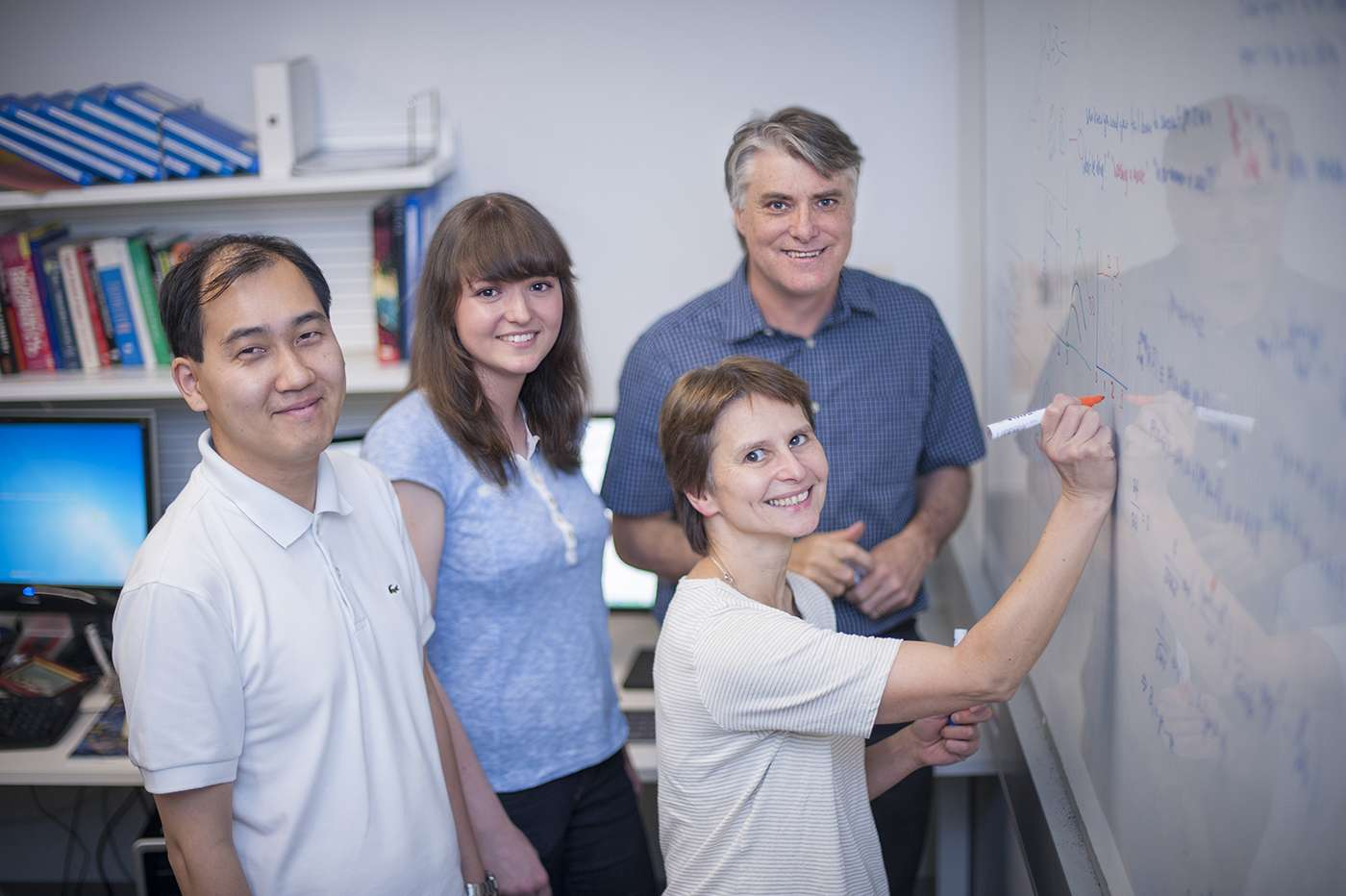 A group of researchers writing on a whiteboard.