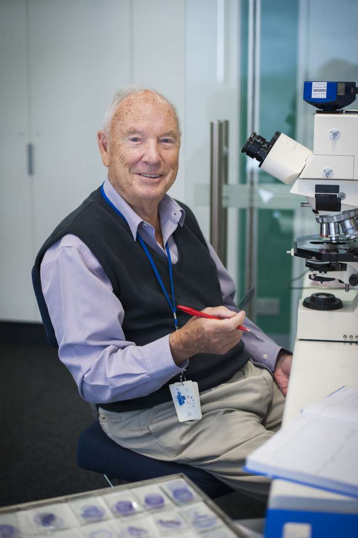 Photograph of Professor Don Metcalf, smiling, sitting at his microscope.