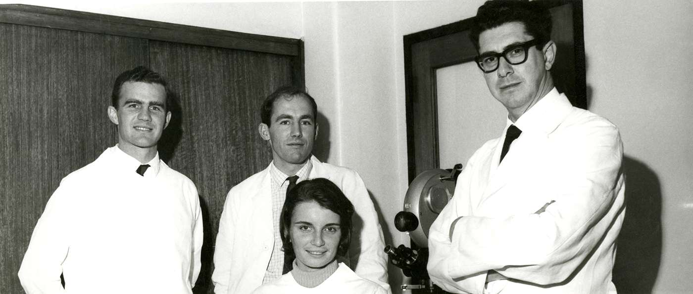 A black and white photo taken in 1967. The male scientists stand, wearing ties and lab coats. The female scientist is seated.