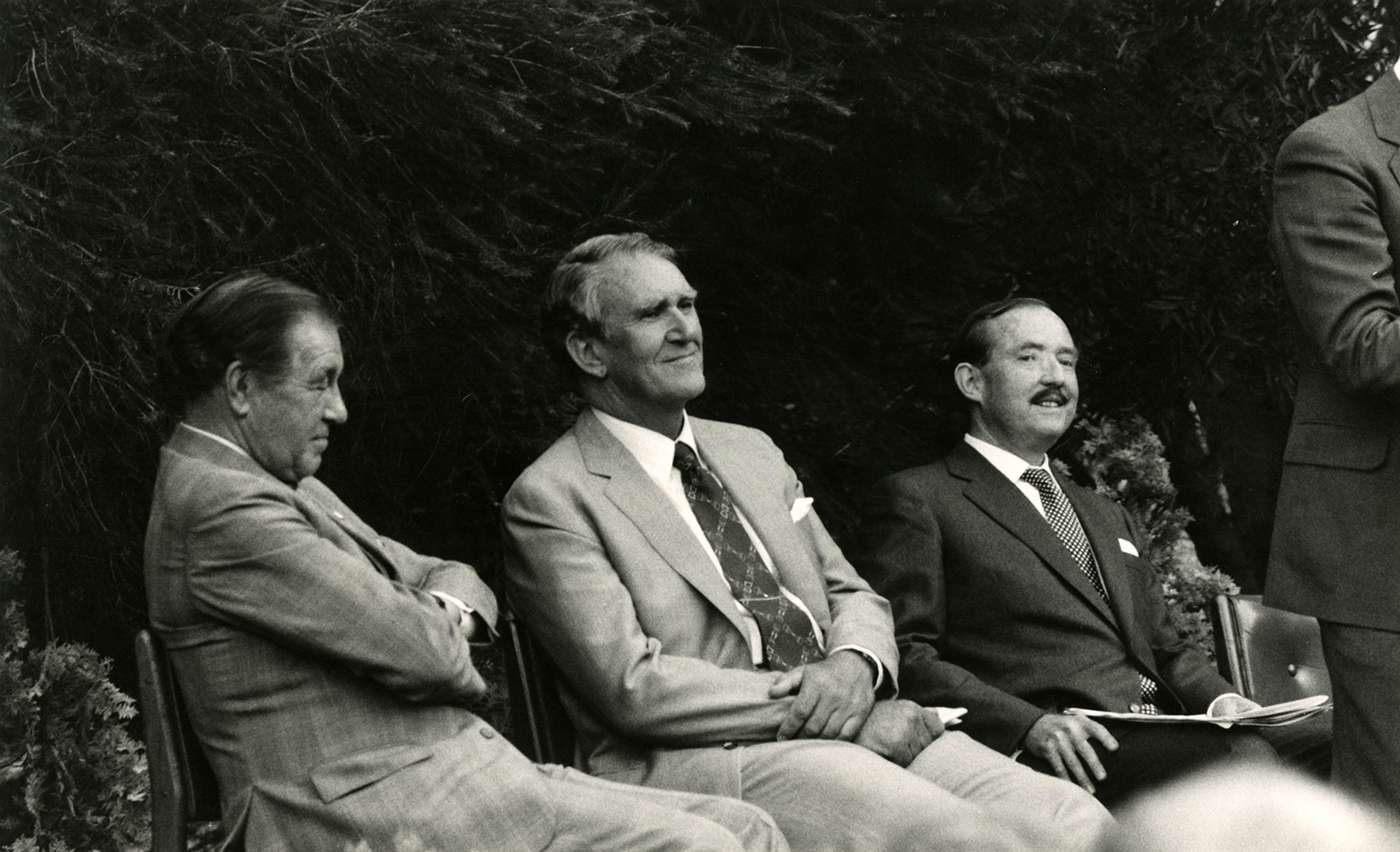 The three men, dressed in suits, sit looking at the speaker (out of shot Sir Gustav Nossal).