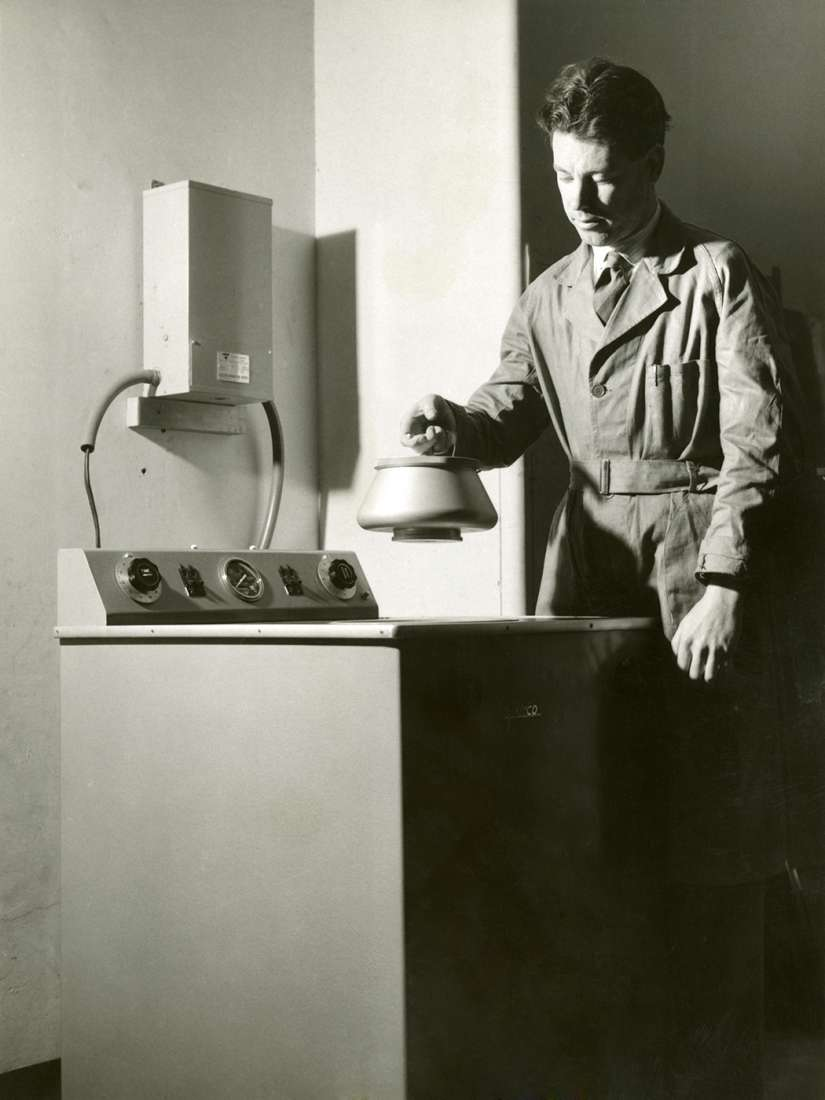 Gordon Ada holding small round rotor over a large piece of equipment called an ultracentrifuge.