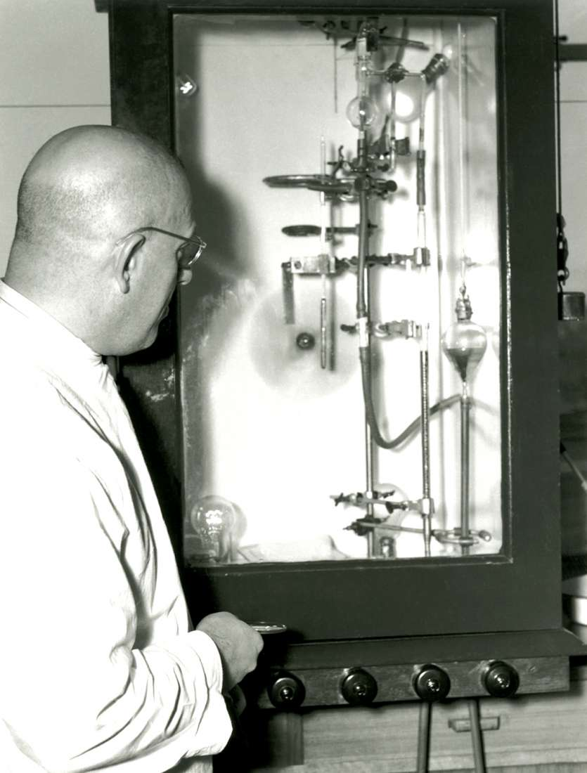 Alfred Gottschalk facing a piece of research equipment with many bottles containing liquid and stands.