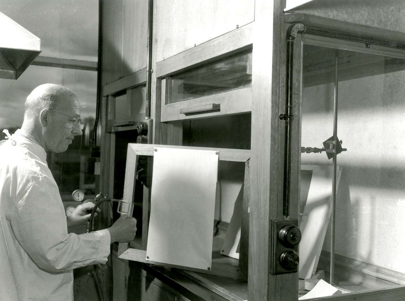 Alfred Gottschalk standing in the lab, spraying a paper chromatogram with dye as part of an experiment.