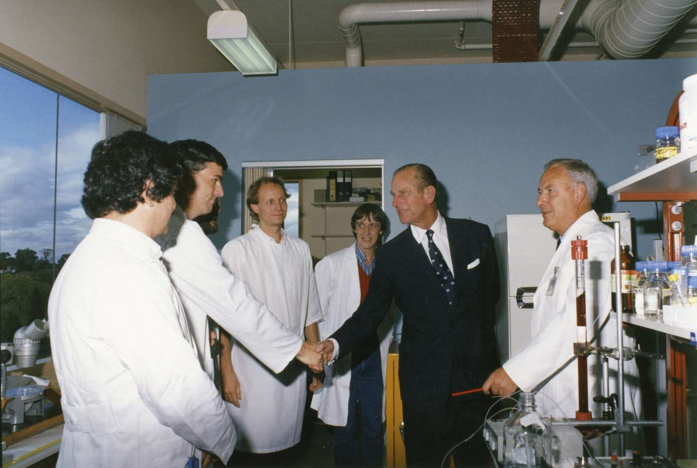 Scientists in white lab coats stand in a lab with Prince Phillip in a dark suit.