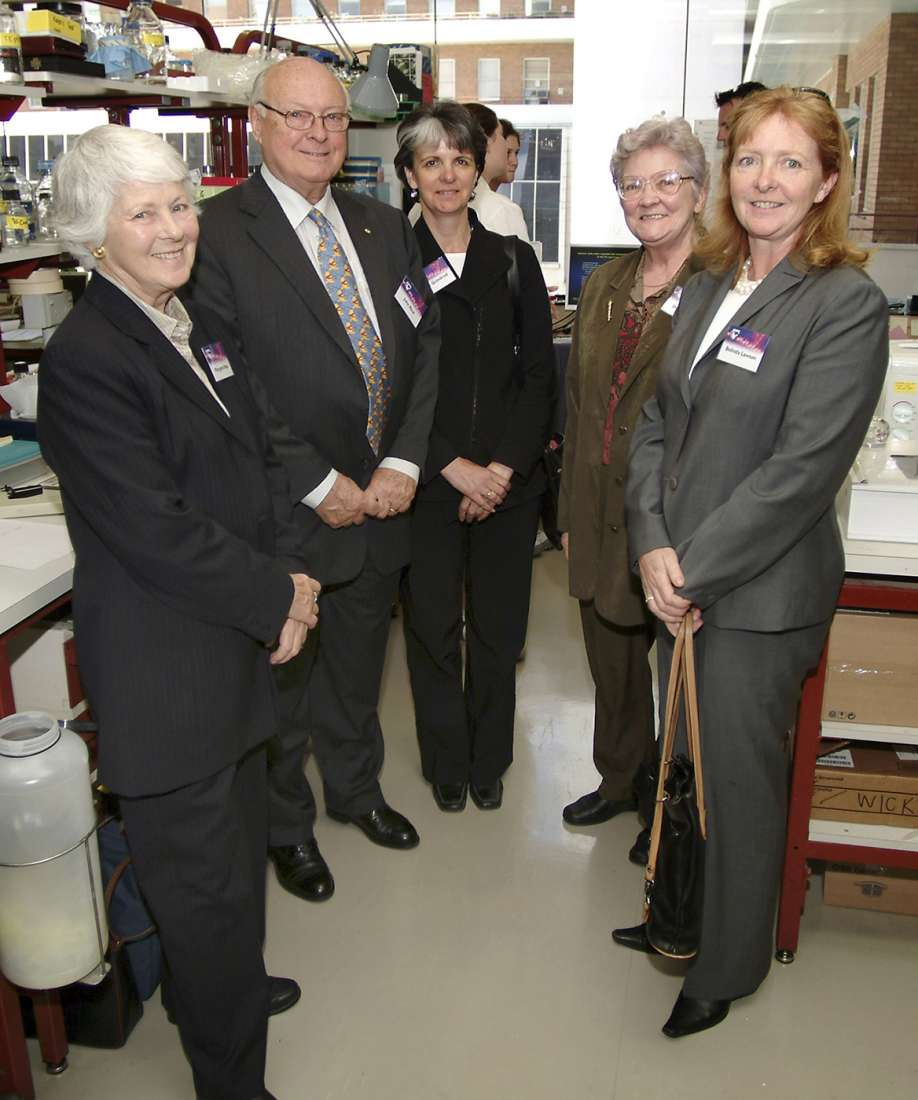 Members stand in the lab, with benches and equipment behind.
