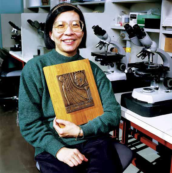 Woman sitting at microscope, lab bench, holding the Burnet Prize plaque.