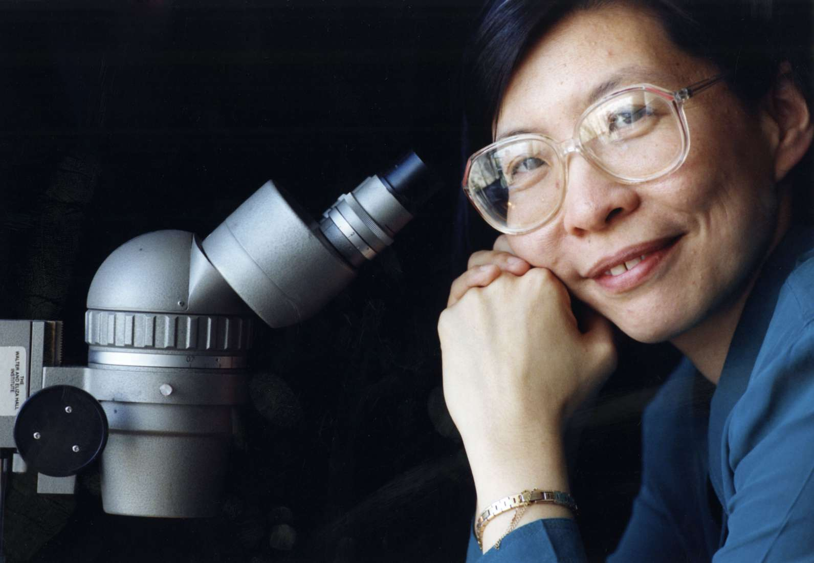Close up image of woman and microscope, credit: The Australian