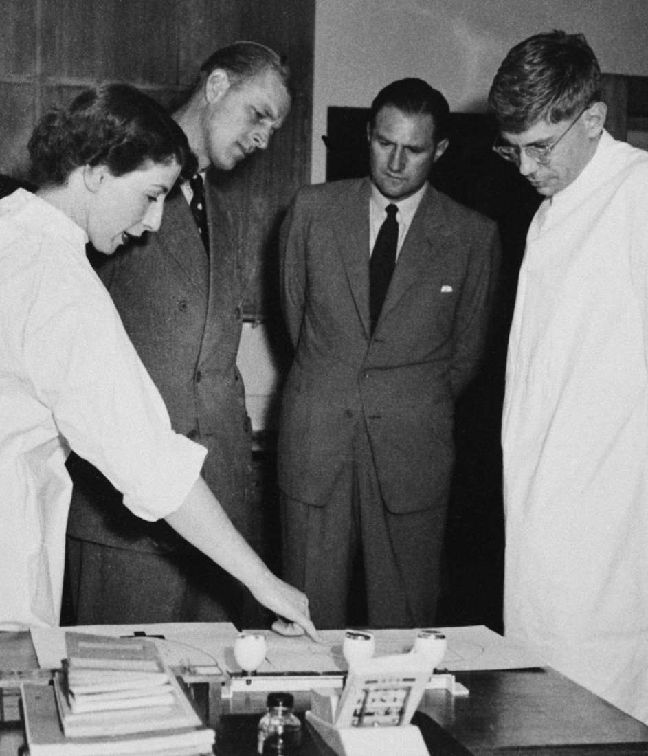 A woman and a man in laboratory coats pointing to an experiment, being viewed by Prince Philip, Duke of Edinburgh, with several other onlookers. Black and white.