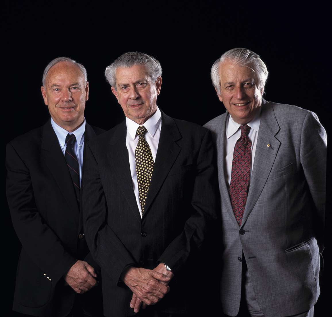 Colour portrait of the retired professors against a black background.