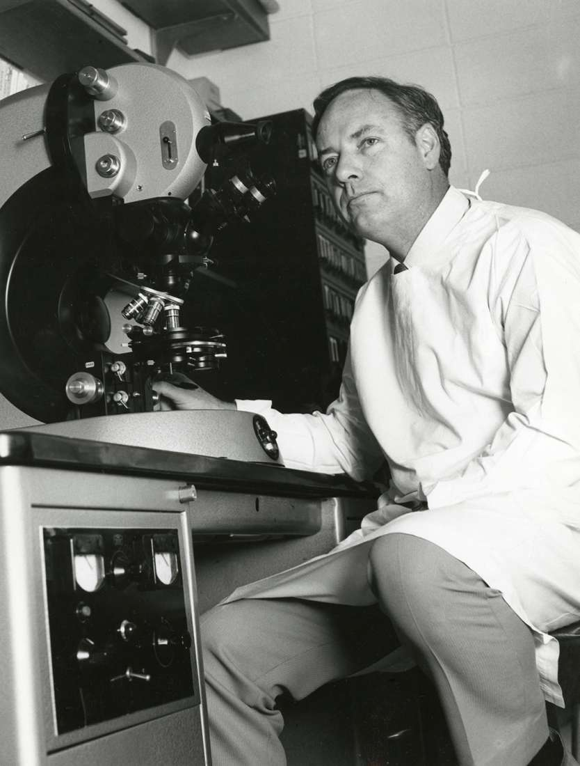 Donald Metcalf sitting at an electron microscope