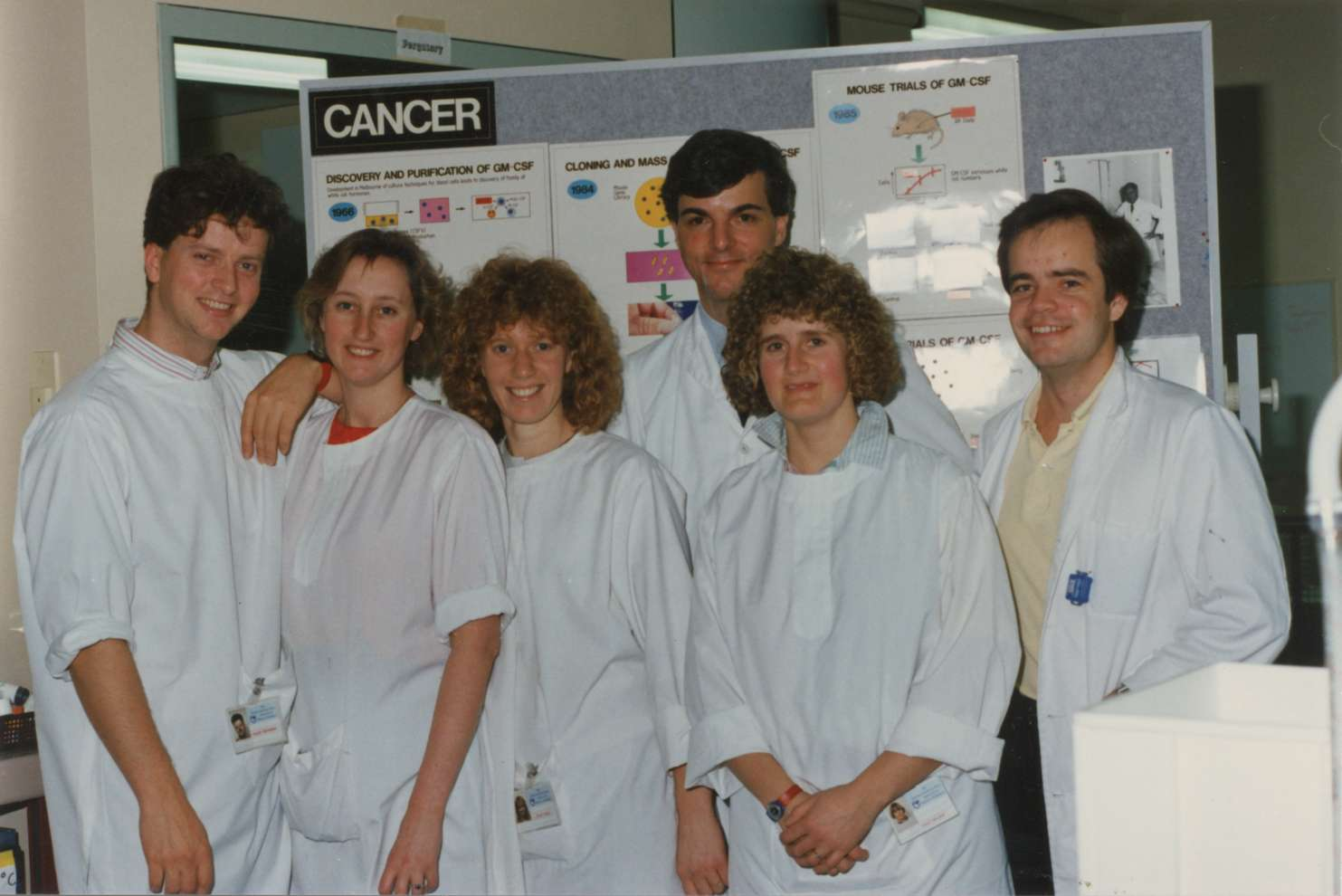 The group stand in front of a poster board, all wearing white lab coats.