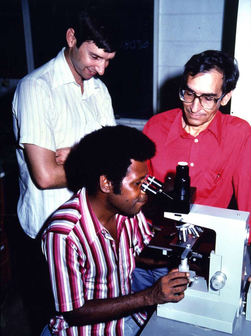 Brown (wearing a white shirt) stands beside a research assistant, both watch a scientist looking down a microscope.
