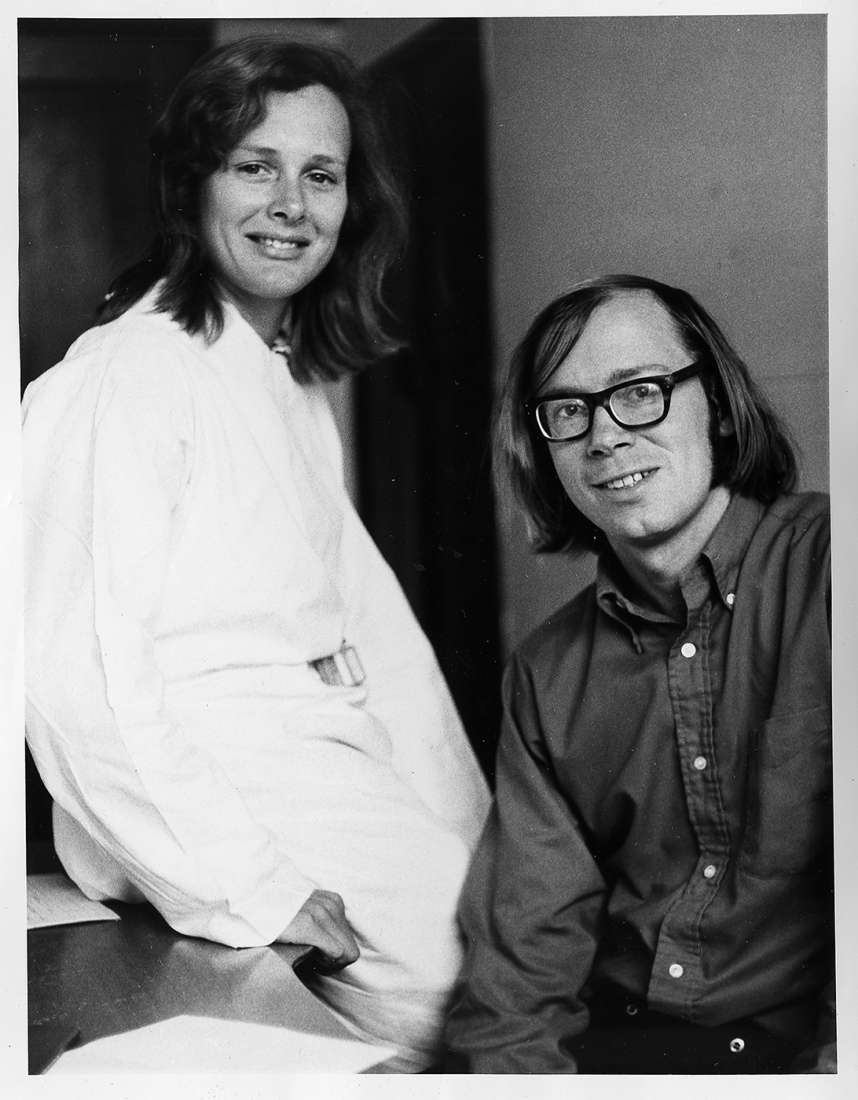 Suzanne Cory sitting on a desk beside Jerry Adams sitting in a chair, groundbreaking, fashionable, long haired scientists.