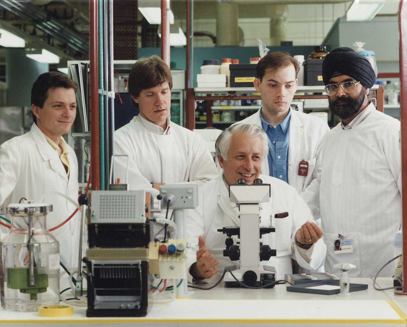 Researchers in the lab, with Gus Nossal seated at microscope.
