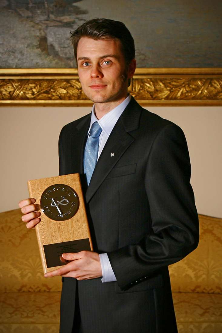 Majewski, wearing a suit, holds the prize plaque in Government House, he was one of six Victorian scientists to win the award.