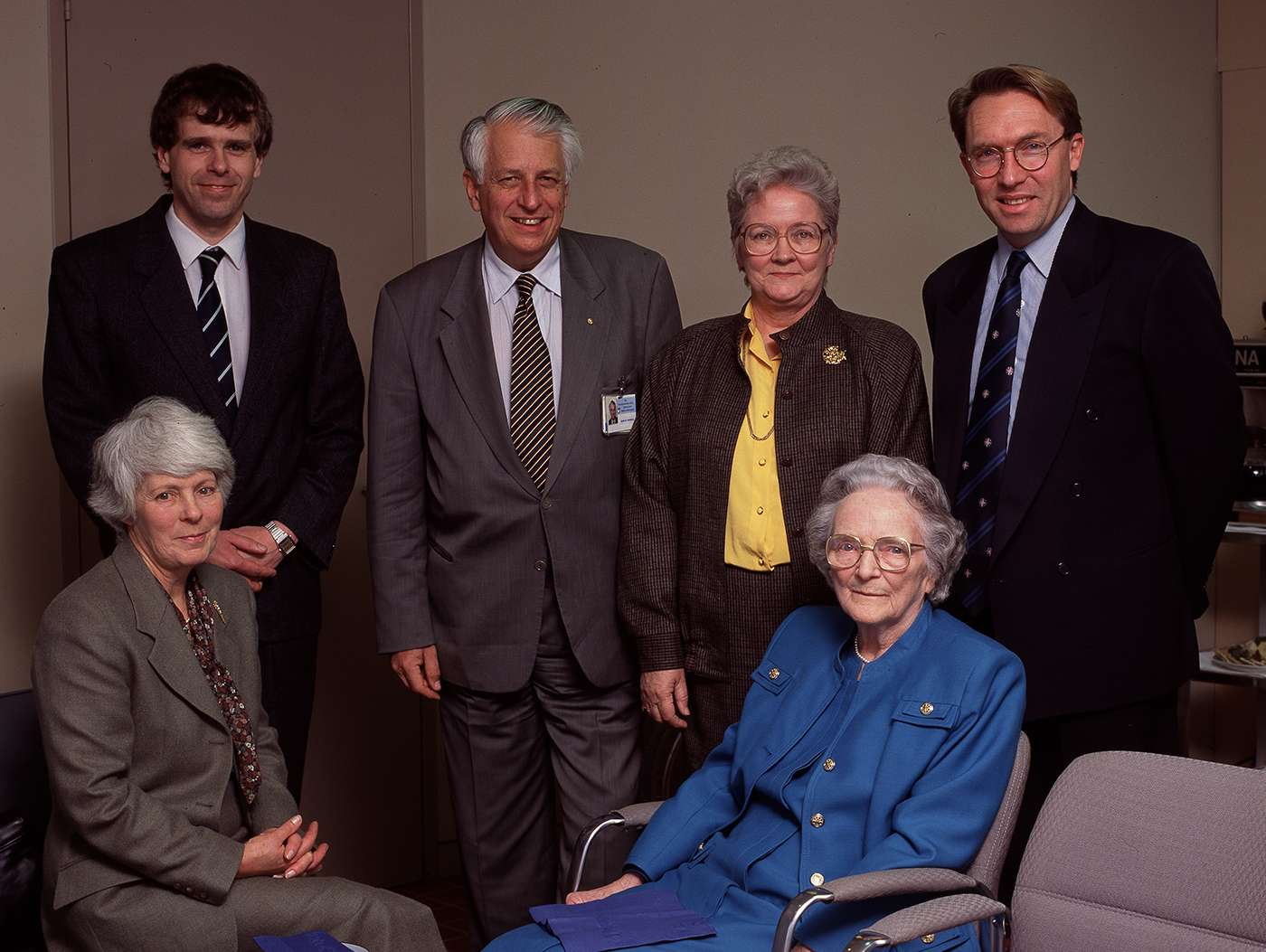 Group of people, two sitting, four standing, smiling facing camera.