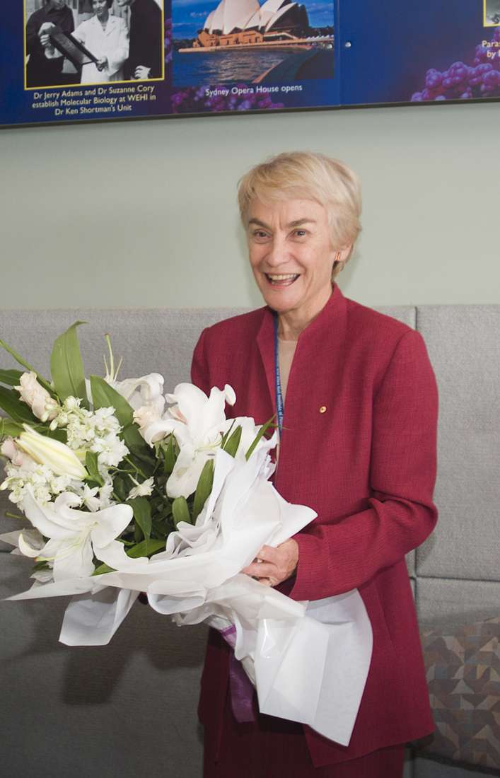 Margret Brumby stands smiling in a red suit jacket with a bunch of white flowers.