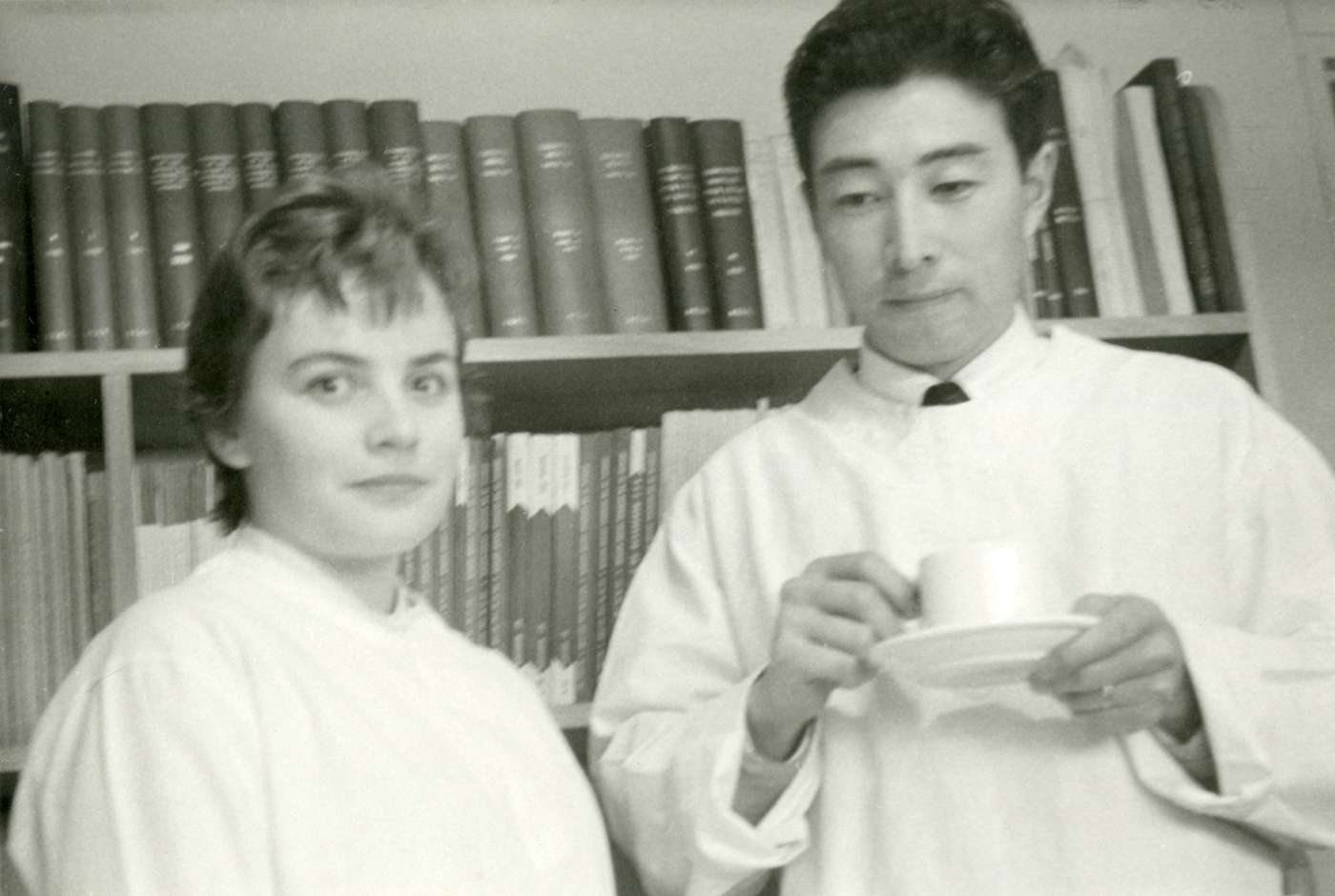 Black and white photograph, both wear lab gowns and stand in an office, Ishidate holds a tea cup and saucer.