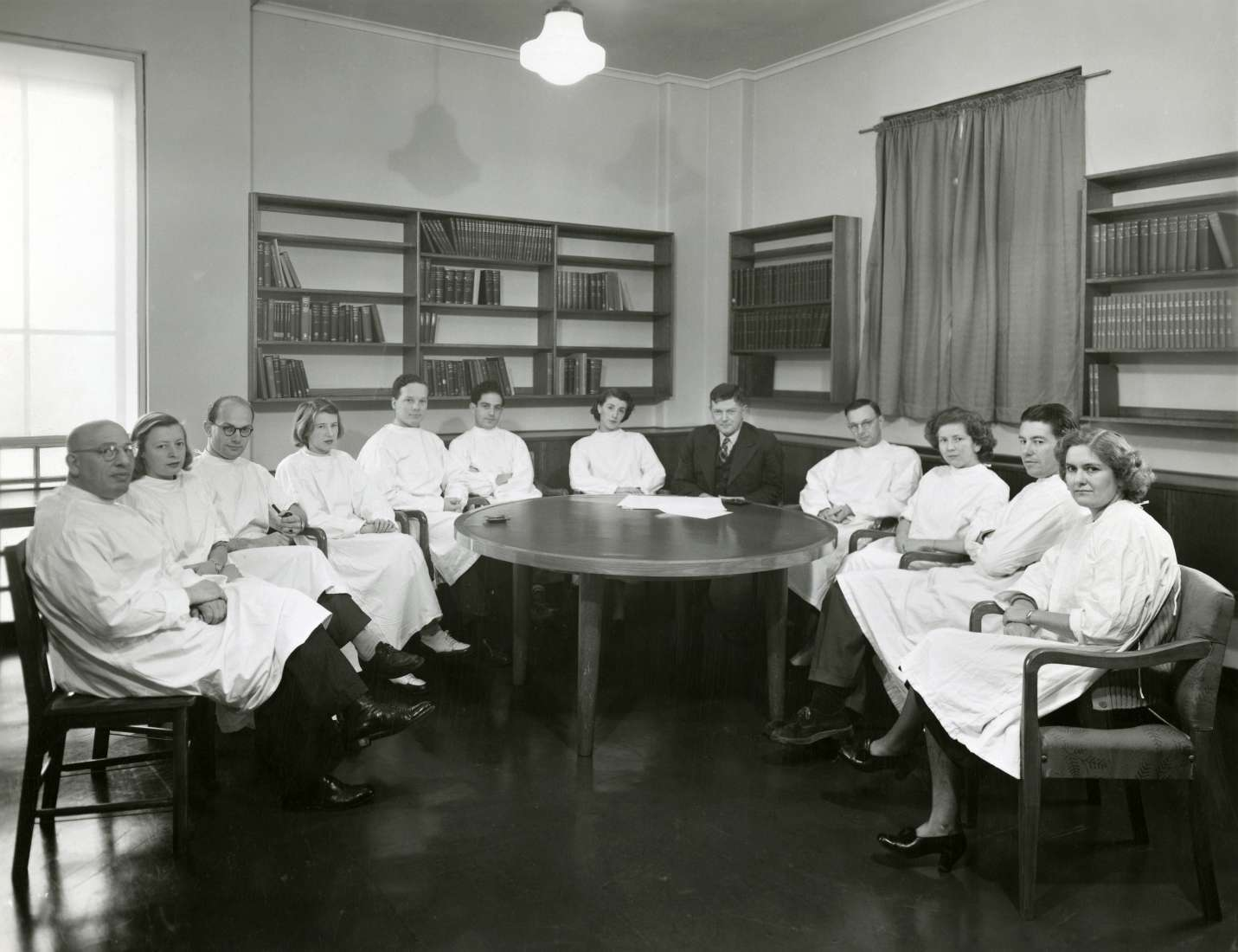 A large group of scientists pictured seated around a table, wearing lab coats. Sir Frank Macfarlane Burnet wears a suit